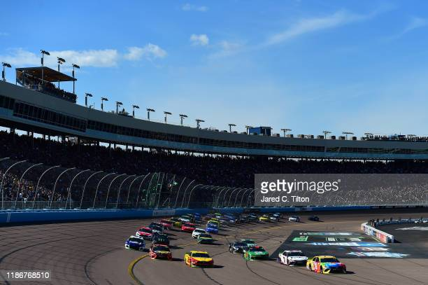 Kyle Busch, driver of the M&M's Toyota, and Joey Logano, driver of the Shell Pennzoil Ford, lead the field to turn one after taking the green flag to...
