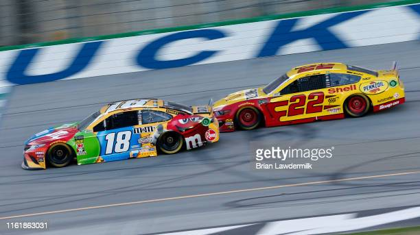 Kyle Busch driver of the MM's Toyota Camry Toyota leads Joey Logano driver of the Shell Pennzoil Ford during the Monster Energy NASCAR Cup Series...