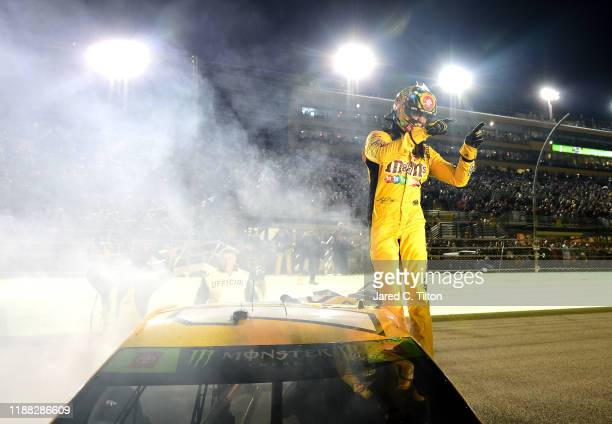 Kyle Busch, driver of the M&M's Toyota, celebrates after winning the Monster Energy NASCAR Cup Series Ford EcoBoost 400 and the Monster Energy NASCAR...