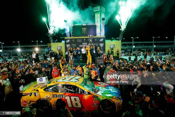 Kyle Busch, driver of the M&M's Toyota, celebrates in Victory Lane after winning the Monster Energy NASCAR Cup Series Ford EcoBoost 400 and the...