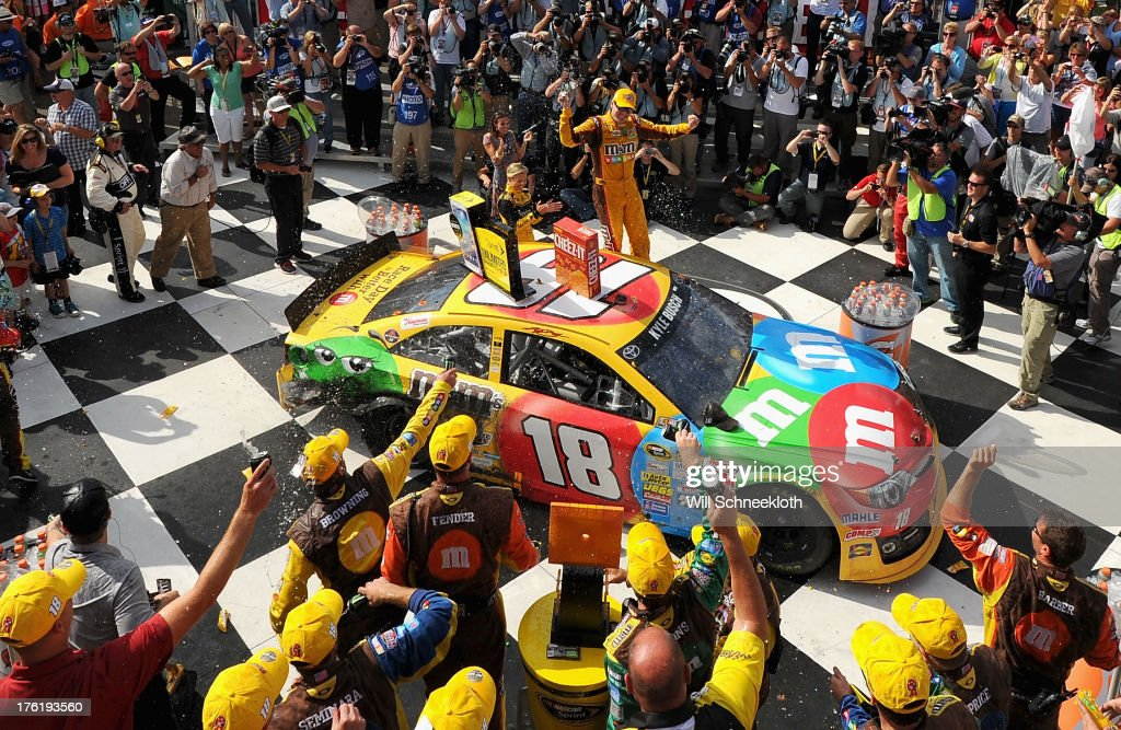 Kyle Busch, driver of the #18 M&M's Toyota, celebrates in Victory Lane after winning during the NASCAR Sprint Cup Series Cheez-It 355 at The Glen at Watkins Glen International on August 11, 2013 in Watkins Glen, New York.