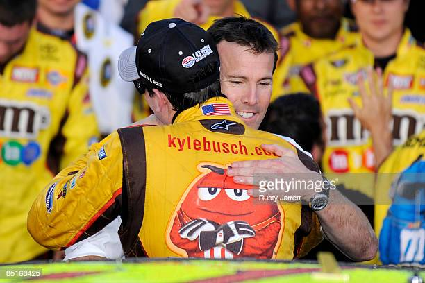 Kyle Busch driver of the MM's Toyota celebrates in victory lane with Team President JD Gibbs after winning the NASCAR Sprint Cup Series Shelby 427 at...