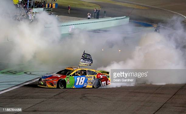 Kyle Busch driver of the MM's Toyota celebrates with a burnout after winning the Monster Energy NASCAR Cup Series Championship and the Monster Energy...
