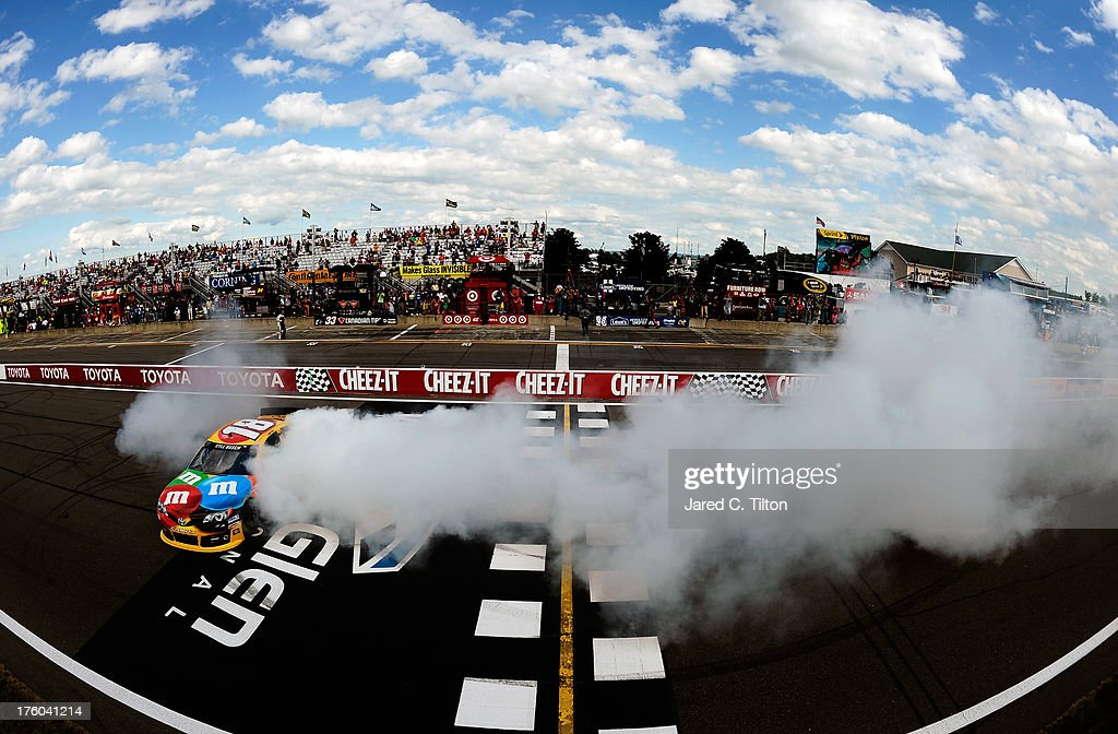 Kyle Busch, driver of the #18 M&M's Toyota, celebrates with a burnout after winning the NASCAR Sprint Cup Series Cheez-It 355 at The Glen at Watkins Glen International on August 11, 2013 in Watkins Glen, New York.