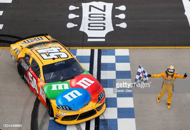 Kyle Busch, driver of the M&M's Toyota, celebrates with the checkered flag after winning the NASCAR Xfinity Series Tennessee Lottery 250 at Nashville...
