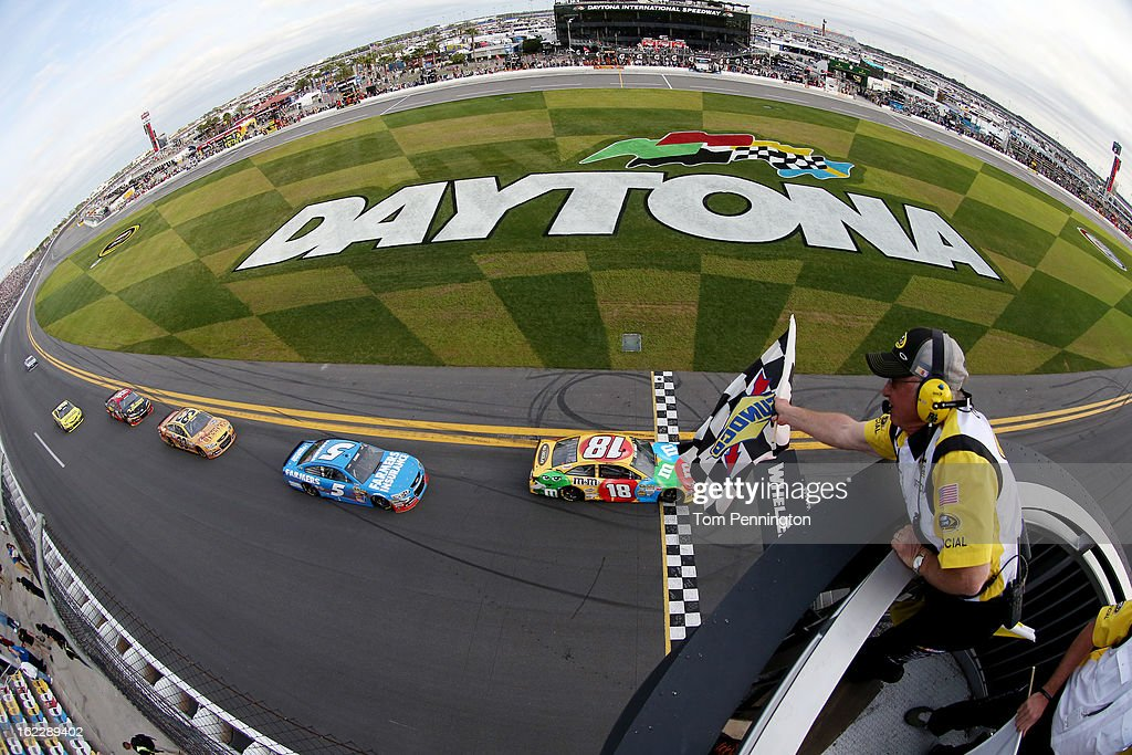 Kyle Busch, driver of the #18 M&M's Toyota, crosses the finish line to take the checkered flag to win the NASCAR Sprint Cup Series Budweiser Duel 2 at Daytona International Speedway on February 21, 2013 in Daytona Beach, Florida.
