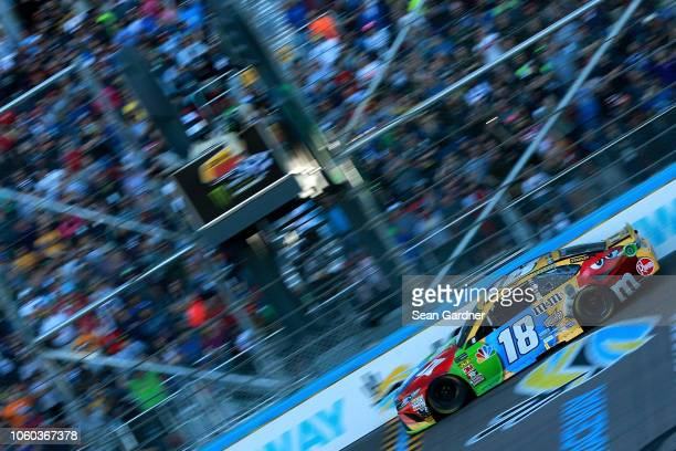 Kyle Busch driver of the MM's Toyota crosses the finish line to win the Monster Energy NASCAR Cup Series CanAm 500 at ISM Raceway on November 11 2018...