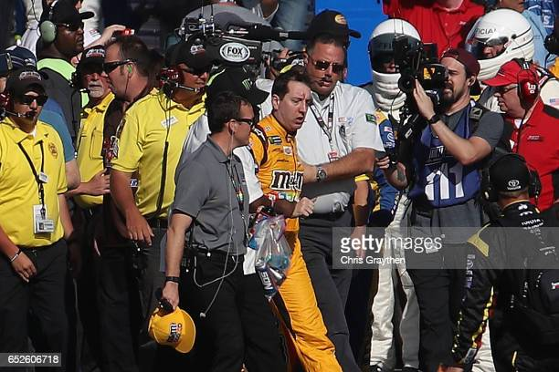 Kyle Busch, driver of the M&M's Toyota, is escorted away by a NASCAR official after an incident on pit road with Joey Logano , driver of the Pennzoil...