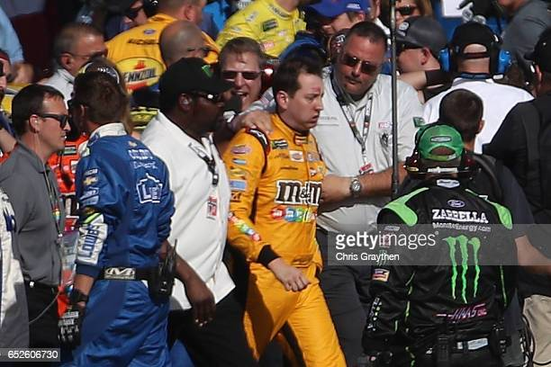 Kyle Busch driver of the MM's Toyota is escorted away by a NASCAR official after an incident on pit road with Joey Logano driver of the Pennzoil Ford...