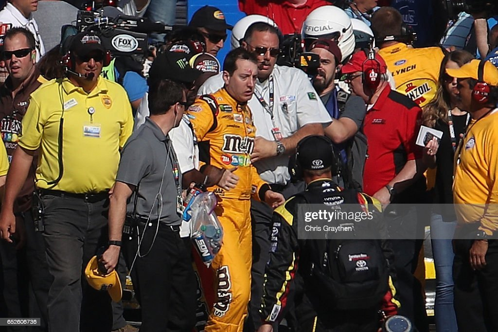 Kyle Busch, driver of the #18 M&M's Toyota, is escorted away by a NASCAR official after an incident on pit road with Joey Logano (not pictured), driver of the #22 Pennzoil Ford, following the Monster Energy NASCAR Cup Series Kobalt 400 at Las Vegas Motor Speedway on March 12, 2017 in Las Vegas, Nevada. Busch and Logano made contact on the track during the last lap of the race leading to the incident on pit road.
