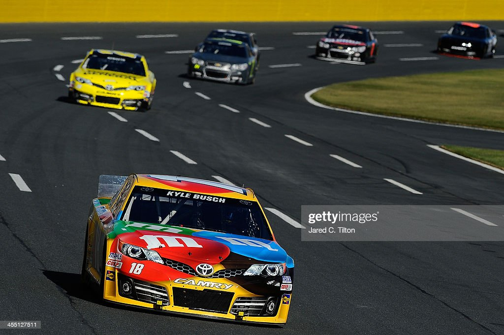 Kyle Busch, driver of the #18 M&M's Toyota, leads a pack of cars during testing at Charlotte Motor Speedway on December 11, 2013 in Charlotte, North Carolina.