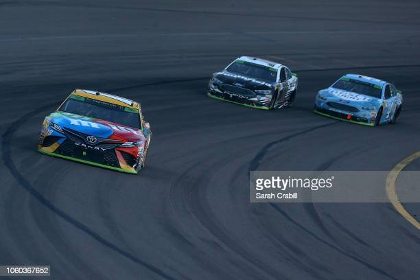 Kyle Busch driver of the MM's Toyota leads Aric Almirola driver of the Smithfield Ford and Kevin Harvick driver of the Busch Light Ford during the...