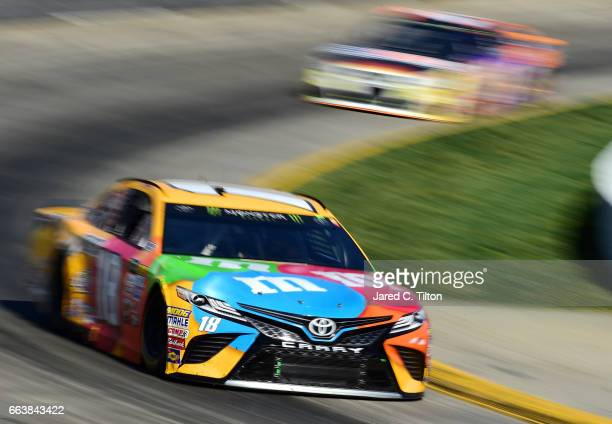 Kyle Busch driver of the MM's Toyota leads Chase Elliott driver of the SunEnergy1 Chevrolet during the Monster Energy NASCAR Cup Series STP 500 at...