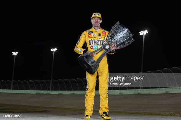 Kyle Busch, driver of the M&M's Toyota poses with the trophy after winning the Monster Energy NASCAR Cup Series Championship at Homestead Speedway on...