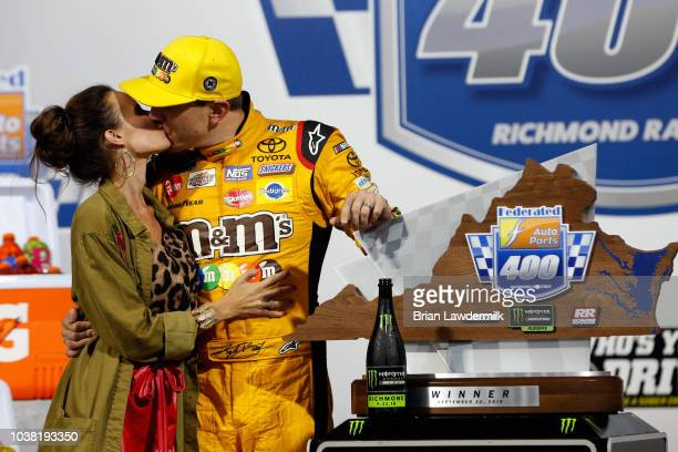 Kyle Busch driver of the MM's Toyota poses with the trophy in Victory Lane with wife Samantha after winning the Monster Energy NASCAR Cup Series...