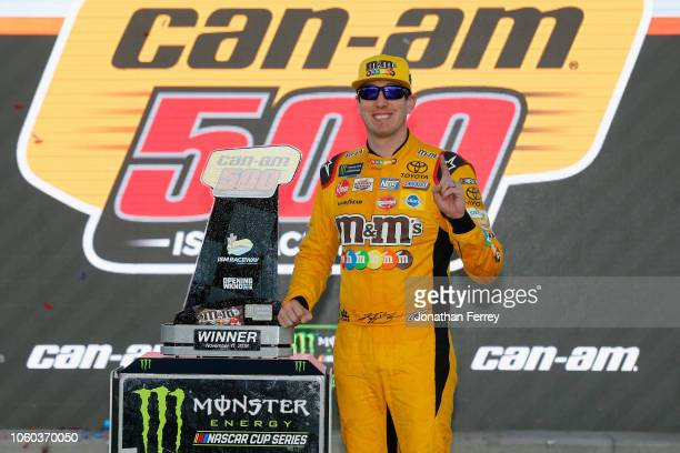 Kyle Busch driver of the MM's Toyota poses with the trophy in Victory Lane after winning the Monster Energy NASCAR Cup Series CanAm 500 at ISM...