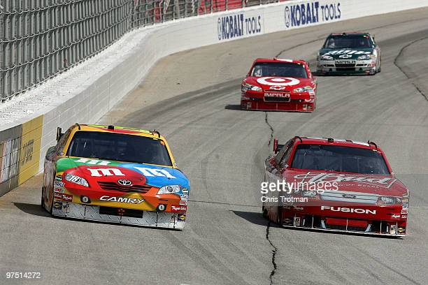 Kyle Busch, driver of the M&M's Toyota, races Kasey Kahne, driver of the Budweiser Ford, side by side ahead of Juan Pablo Montoya, driver of the...