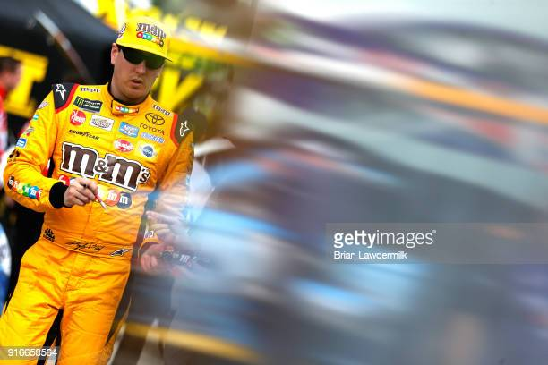 Kyle Busch driver of the MM's Toyota stands in the garage during practice for the Monster Energy NASCAR Cup Series Daytona 500 at Daytona...
