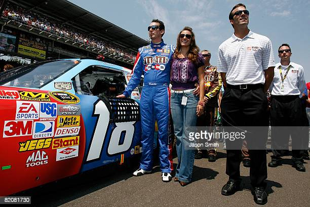 Kyle Busch driver of the MM's Toyota stands with Samantha Sarcinella and JD Gibbs President of Joe Gibbs Racing during prerace activities for the...
