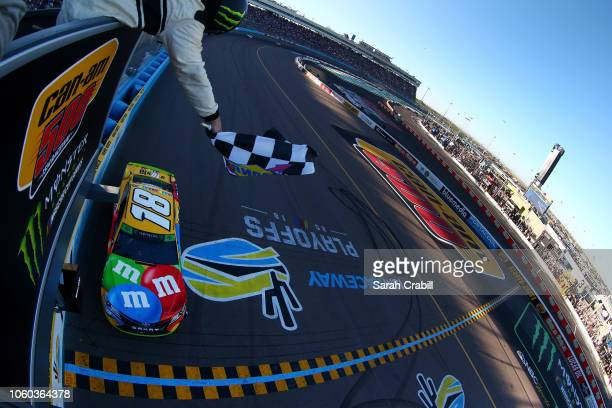 Kyle Busch driver of the MM's Toyota takes the checkered flag to win the Monster Energy NASCAR Cup Series CanAm 500 at ISM Raceway on November 11...
