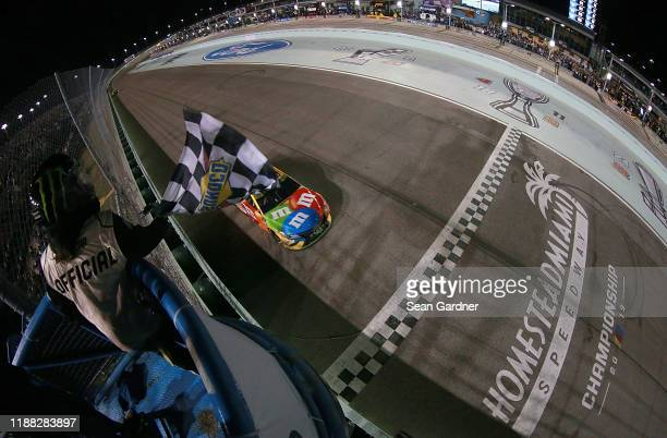 Kyle Busch, driver of the M&M's Toyota, takes the checkered flag to win the Monster Energy NASCAR Cup Series Championship and the Monster Energy...