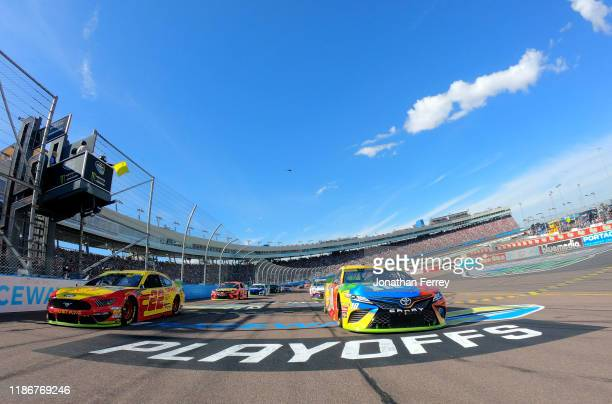 Kyle Busch, driver of the M&M's Toyota,and Joey Logano, driver of the Shell Pennzoil Ford, lead the field to the green flag at the satrt of the...