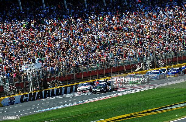 Kyle Busch, driver of the Monster Energy Toyota, and Brad Keselowski, driver of the Discount Tire Ford, lead the field past the green flag to start...
