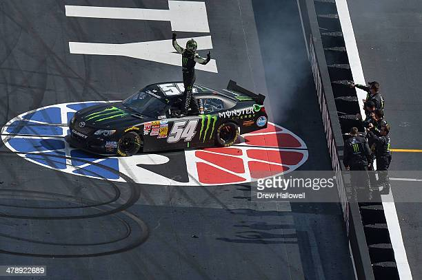 Kyle Busch driver of the Monster Energy Toyota and his crew members celebrate with after bow after winning the NASCAR Nationwide Series Drive To Stop...