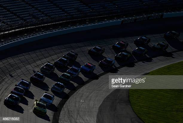 Kyle Busch driver of the Monster Energy Toyota and Joey Logano driver of the Hertz Ford lead the field to a restart during the NASCAR Nationwide...