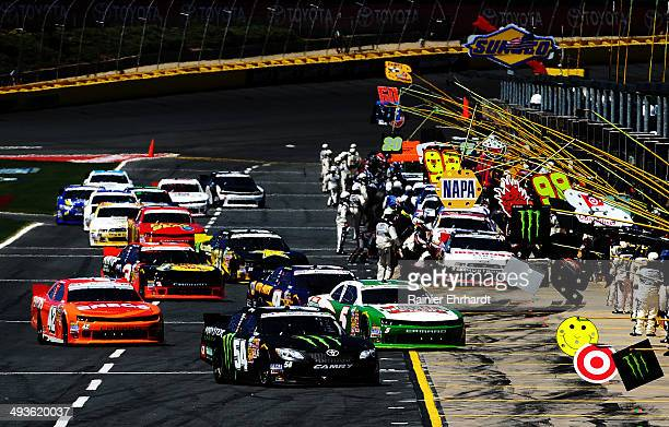 Kyle Busch, driver of the Monster Energy Toyota, and others pit during the NASCAR Nationwide Series History 300 at Charlotte Motor Speedway on May...