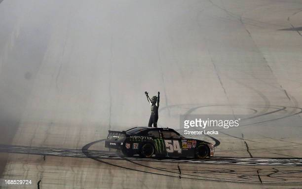 Kyle Busch driver of the Monster Energy Toyota celebrates after performing a burnout following his win in the NASCAR Nationwide Series VFW Sport...