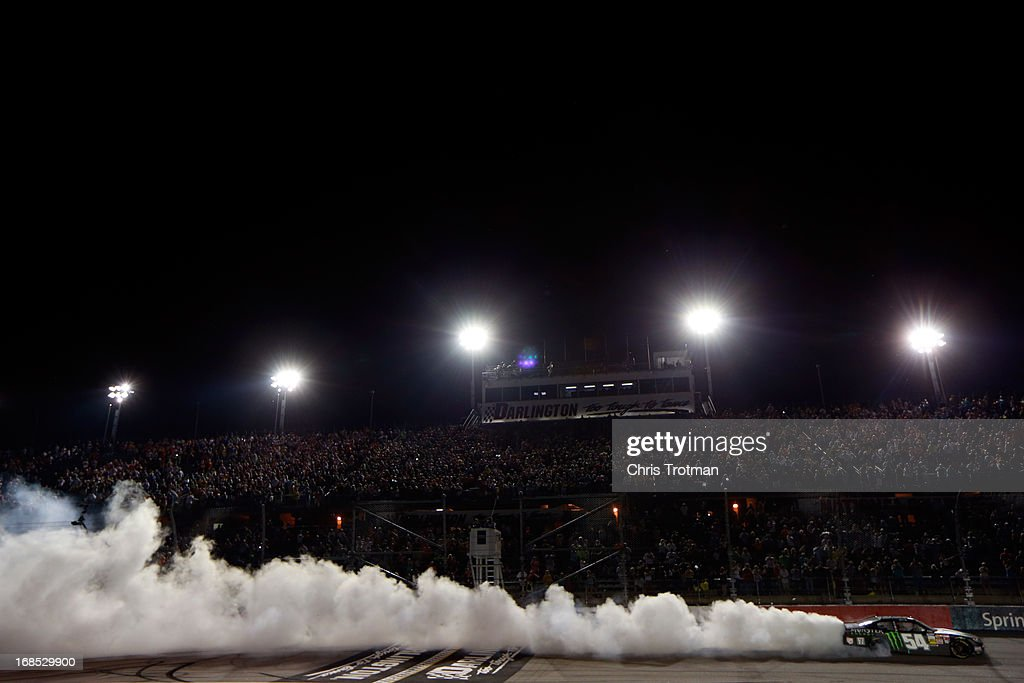 Kyle Busch, driver of the #54 Monster Energy Toyota, celebrates by performing a burnout following his win in the NASCAR Nationwide Series VFW Sport Clips Help A Hero 200 at Darlington Raceway on May 10, 2013 in Darlington, South Carolina.