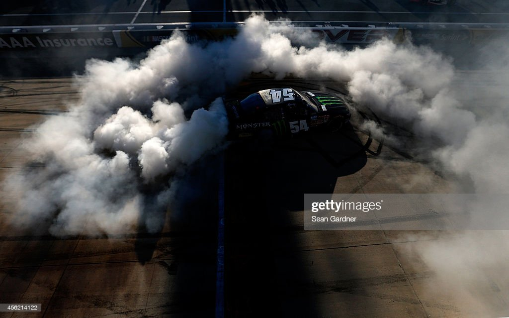 Kyle Busch, driver of the #54 Monster Energy Toyota, celebrates with a burnout after winning the NASCAR Nationwide Series Dover 200 at Dover International Speedway on September 27, 2014 in Dover, Delaware.