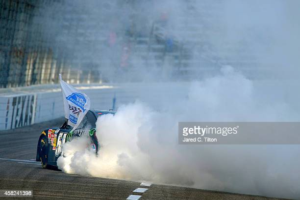 Kyle Busch, driver of the Monster Energy Toyota, celebrates with a burnout after winning the NASCAR Nationwide Series O'Reilly Auto Parts Challenge...