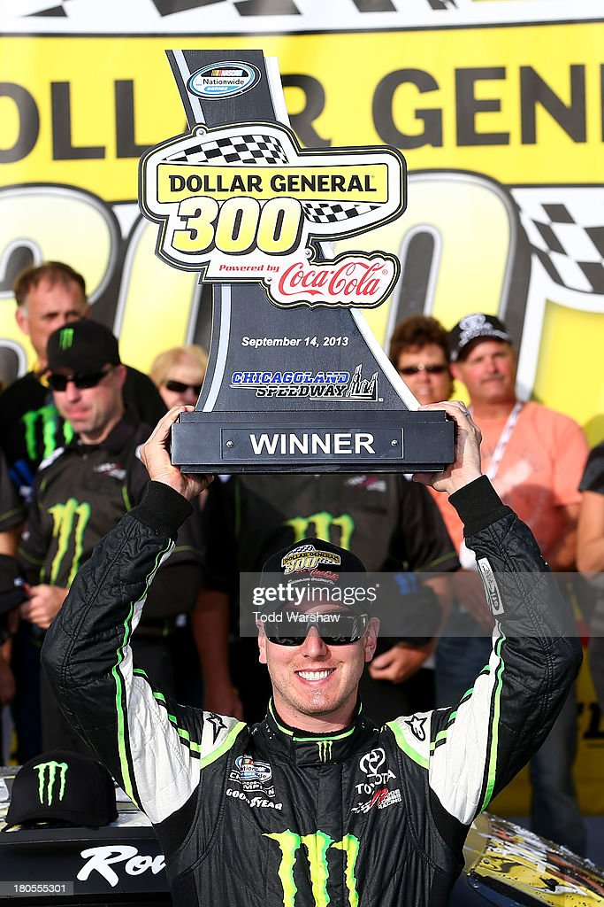 Kyle Busch, driver of the #54 Monster Energy Toyota, celebrates with the trophy in Victory Lane after winning the NASCAR Nationwide Series Dollar General 300 Powered by Coca-Cola at Chicagoland Speedway on September 14, 2013 in Joliet, Illinois.