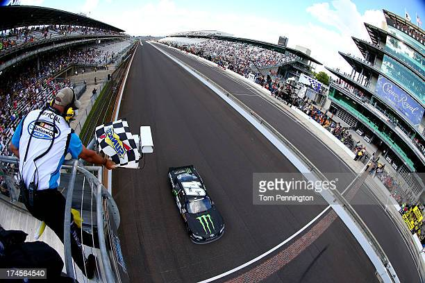 Kyle Busch driver of the Monster Energy Toyota crosses the finish line to win the NASCAR Nationwide Series Indiana 250 at Indianapolis Motor Speedway...