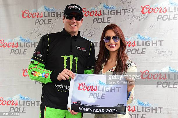 Kyle Busch driver of the Monster Energy Toyota poses with Miss Coors Light Amanda Mertz and the Coors Light Pole award after qualifying for pole...
