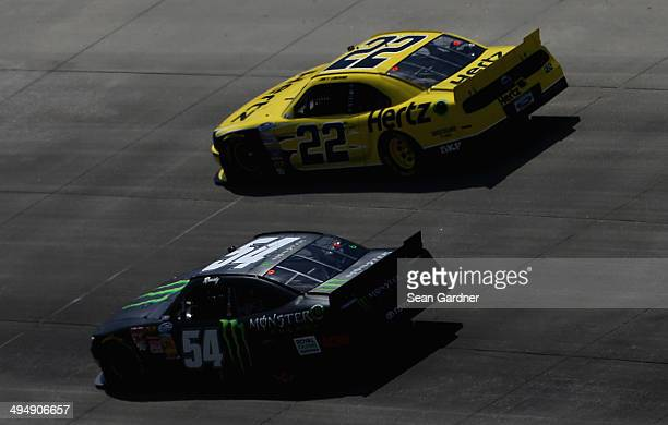 Kyle Busch driver of the Monster Energy Toyota races Joey Logano driver of the Hertz Ford during the NASCAR Nationwide Series Buckle Up 200 Presented...