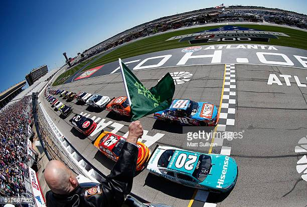 Kyle Busch, driver of the NOS Energy Drink Toyota, and Erik Jones, driver of the Hisense USA Toyota, lead the field past the green flag to start the...