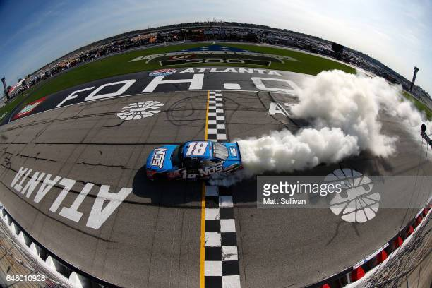Kyle Busch driver of the NOS Energy Drink Toyota celebrates with a burnout after winning the NASCAR XFINITY Series Rinnai 250 at Atlanta Motor...