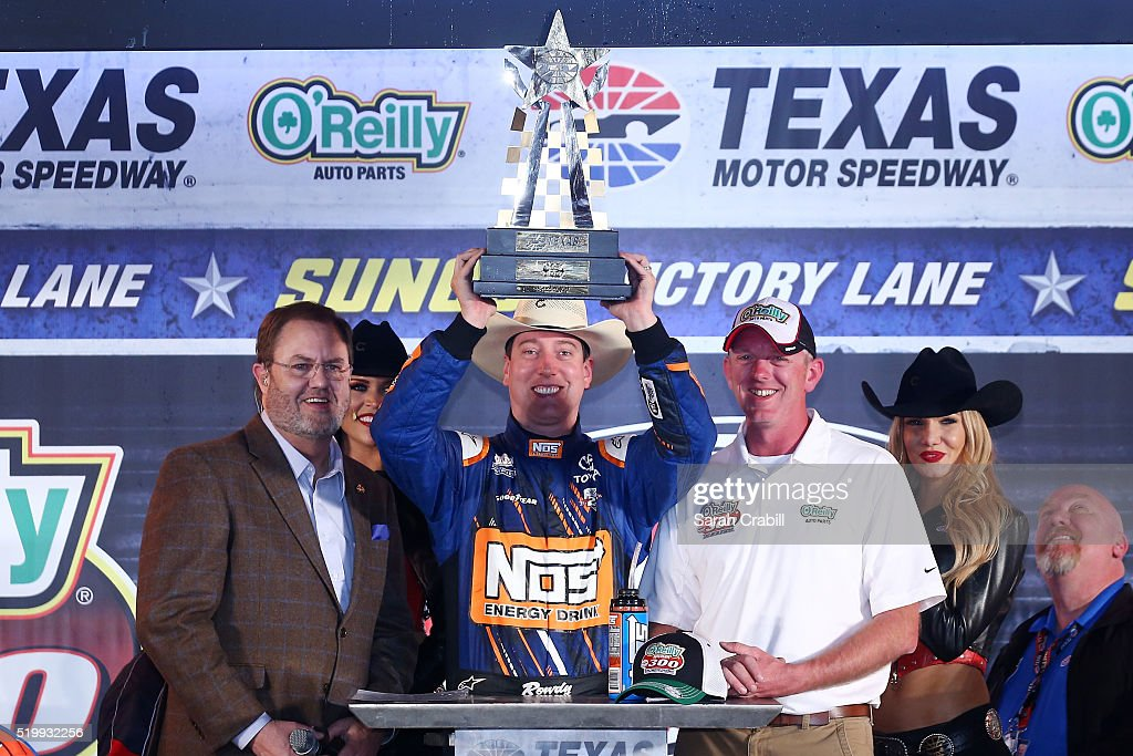 Kyle Busch, driver of the #18 NOS Energy Drink Toyota, celebrates with the trophy in Victory Lane after winning the NASCAR XFINITY Series O'Reilly Auto Parts 300 as Texas Motor Speedway President Eddie Gossage (L) and O'Reilly Auto Parts Event Specialist Shawn Myers (R) look on at Texas Motor Speedway on April 8, 2016 in Fort Worth, Texas.