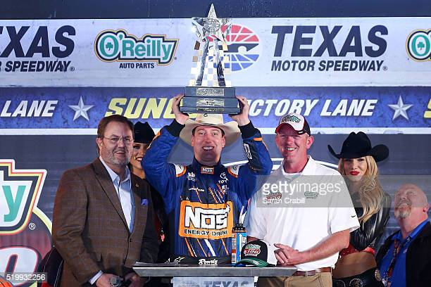 Kyle Busch driver of the NOS Energy Drink Toyota celebrates with the trophy in Victory Lane after winning the NASCAR XFINITY Series O'Reilly Auto...
