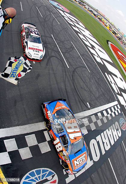 Kyle Busch driver of the NOS Energy Drink Toyota crosses the finish line ahead of Brad Keselowski driver of the Discount Tire Dodge to win the NASCAR...