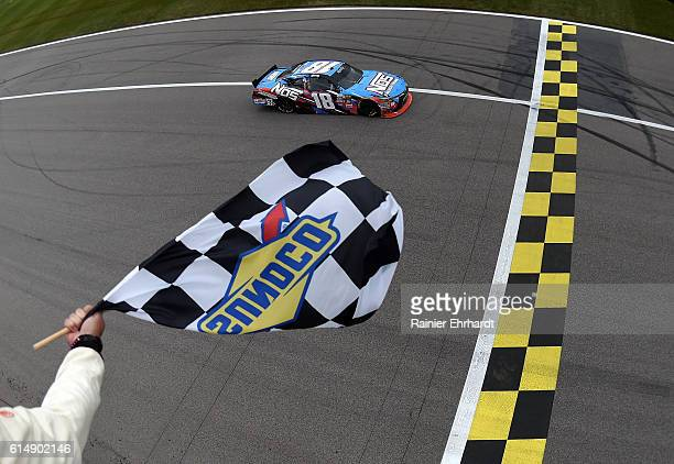 Kyle Busch, driver of the NOS Energy Drink Toyota, crosses the finish line to win the NASCAR XFINITY Series Kansas Lottery 300 at Kansas Speedway on...