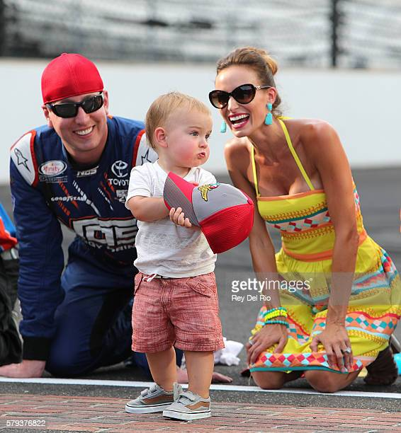 Kyle Busch driver of the NOS Energy Drink Toyota kisses the bricks with his wife Samantha and son Brexton after winning the NASCAR XFINITY Series...