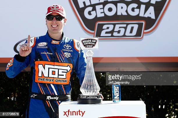 Kyle Busch driver of the NOS Energy Drink Toyota poses in Victory Lane after winning the NASCAR XFINITY Series Heads Up Georgia 250 at Atlanta Motor...