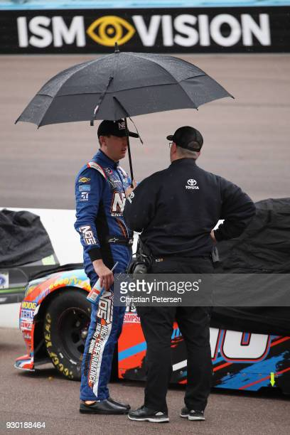 Kyle Busch driver of the NOS Toyota stands on pit road during a red flag for rain during the NASCAR Xfinity Series DC Solar 200 at ISM Raceway on...