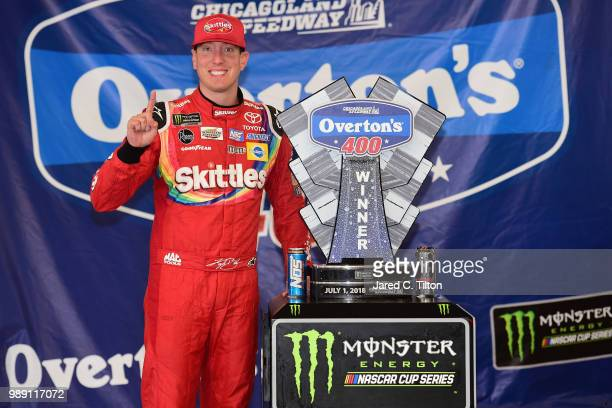 Kyle Busch driver of the Skittles Red White Blue Toyota poses with the trophy after winning the Monster Energy NASCAR Cup Series Overton's 400 at...
