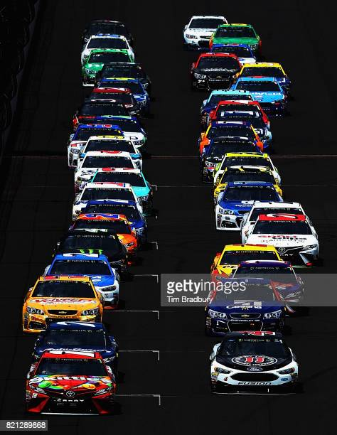 Kyle Busch driver of the Skittles Toyota and Kevin Harvick driver of the Jimmy John's Ford lead the field at the start of the Monster Energy NASCAR...