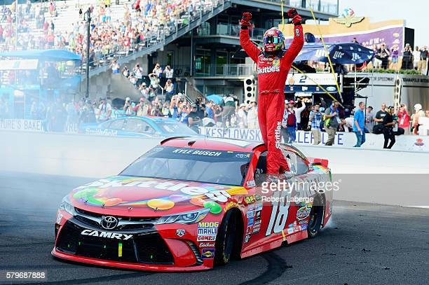 Kyle Busch driver of the Skittles Toyota celebrates winning the NASCAR Sprint Cup Series Crown Royal Presents the Combat Wounded Coalition 400 at...